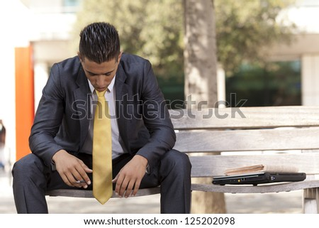 Frustrated businessman sit at the bench park,  smoking a cigar to relax