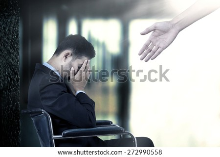Frustrated businessman sitting on a wheelchair,  get a help from a hand - stock photo