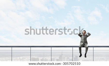 Frustrated businessman sitting on parapet closing ears with hands - stock photo