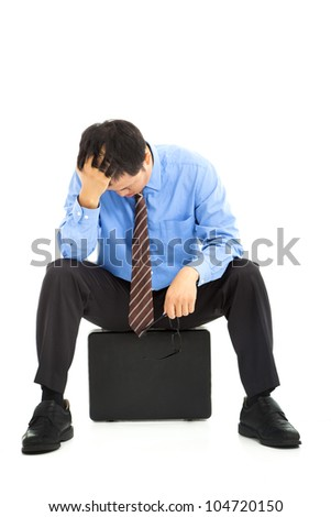 frustrated businessman sitting on the briefcase - stock photo
