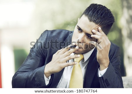 frustrated businessman smoking a cigar to relax