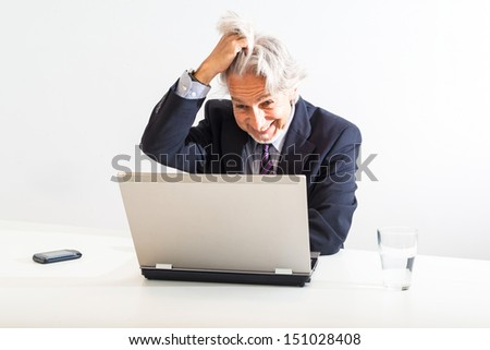 frustrated businessman tearing his hair out behind his laptop in a modern bright office. The white desk is decorated with a glass of water and a mobile phone. - stock photo