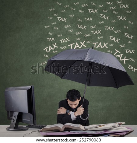 Frustrated businessman using umbrella for protecting him from tax - stock photo