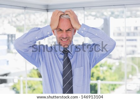 Frustrated businessman with hands on his head looking at camera