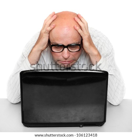 Frustrated businessman with laptop on a desk in the office. - stock photo