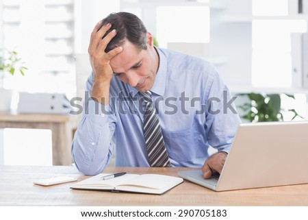 Frustrated businessman working in his office at work