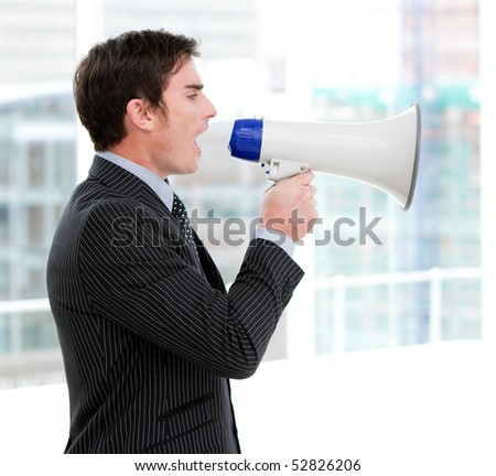 Frustrated businessman yelling through a megaphone standing in the office - stock photo