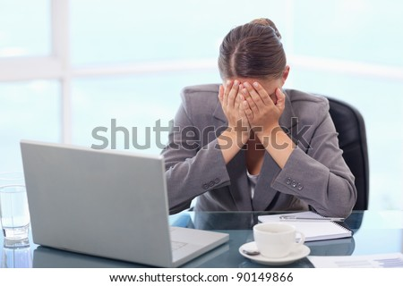Frustrated businesswoman crying in her office