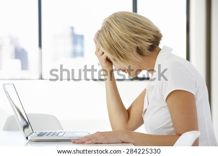 Frustrated Businesswoman Sitting At Desk In Office Using Laptop - stock photo