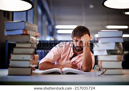 Frustrated college male student studying poorly at late evening, night before exam, male student with pile of books study hard for exam in high school, tired and bored to study hard for exam - stock photo