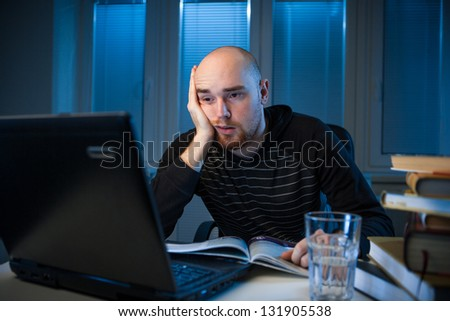 frustrated college student studying poorly at late evening, night before exam, funny night procrastination concept - stock photo