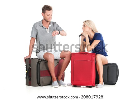 frustrated couple waiting departure with luggage. handsome man looking at watches and sitting - stock photo
