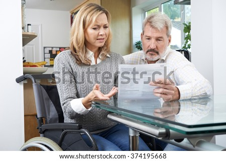 Frustrated Couple With Woman In Wheelchair Reading Letter - stock photo