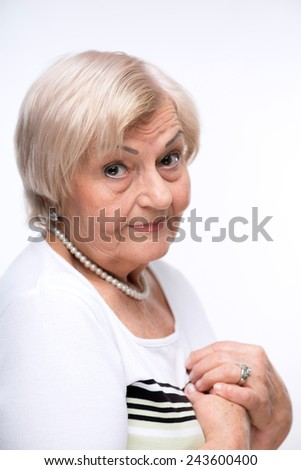 Frustrated elderly woman. Closeup side view shot of senior woman standing with her hands crossed isolated over white backgound - stock photo