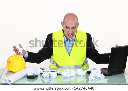 Frustrated engineer at a desk - stock photo