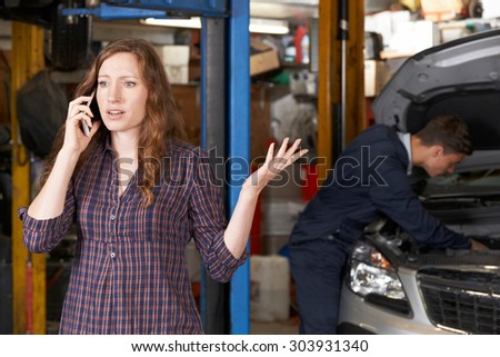 Frustrated Female Customer On Mobile Phone At Auto Repair Shop - stock photo