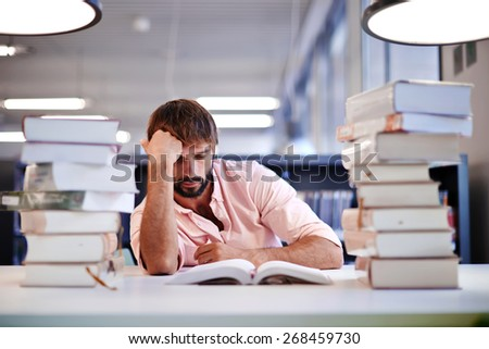 Frustrated male student sitting at the desk with a huge pile of study books in university library, young college student at hard exam preparation in study hall looking tired and weary