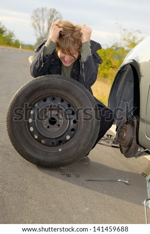 Frustrated man changing wheel on a car - stock photo
