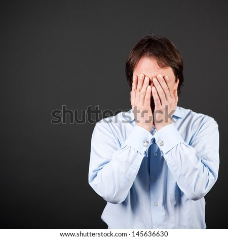 frustrated man putting his hands on his face against black wall - stock photo