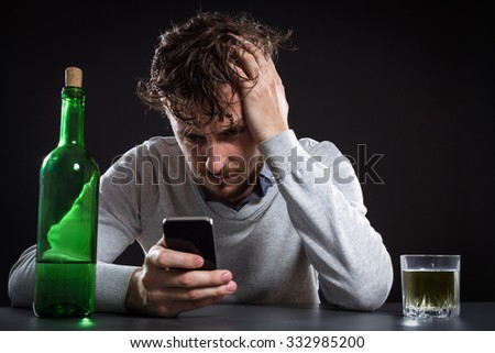 Frustrated Man With Bottle Holding Mobile And Going To Make A Call On Black Background - stock photo