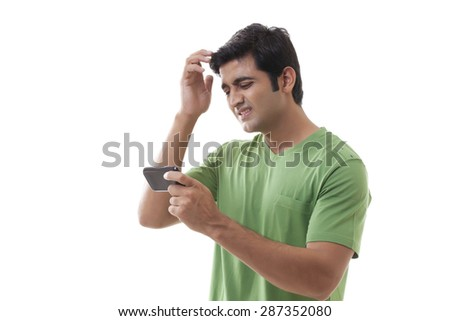 Frustrated man with cellular phone on white background - stock photo