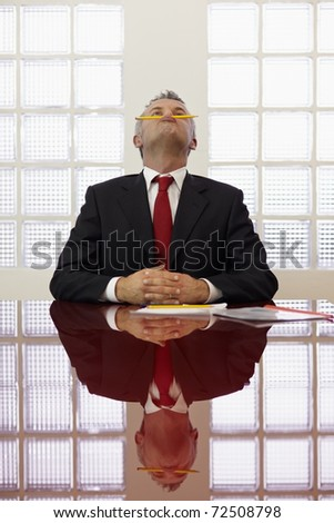 Frustrated mature businessman holding pencil between mouth and nose in office meeting room. Vertical shape, front view, waist up - stock photo