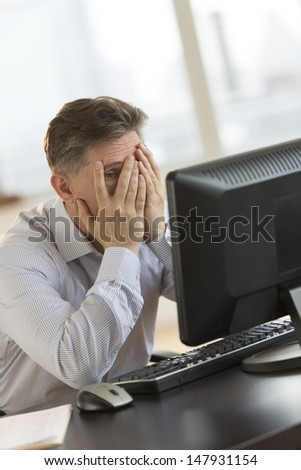 Frustrated mature businessman with hands on face looking at computer at desk in office - stock photo