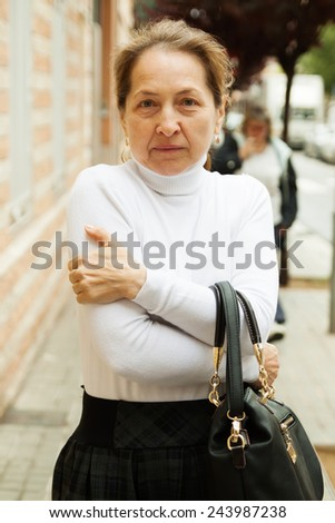 Frustrated mature woman on  sidewalk - stock photo
