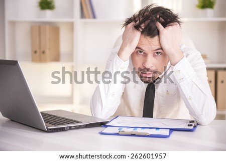 Frustrated middle aged businessman sitting at office desk and looking at camera