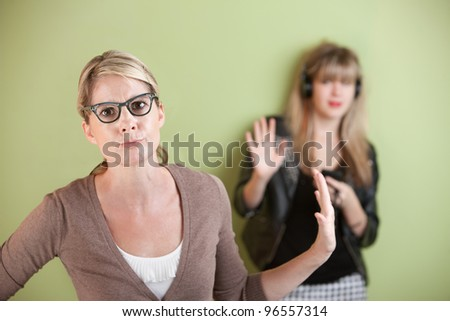Frustrated mom with daughter listening to music on headphones - stock photo