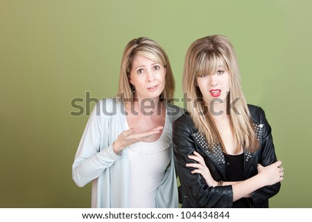 Frustrated mother and daughter over green background