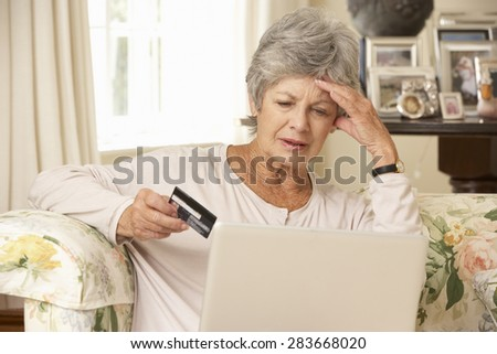 Frustrated Retired Senior Woman Sitting On Sofa At Home Using Laptop - stock photo