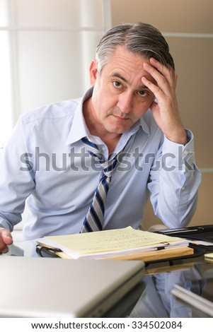 Frustrated stressed business man in an office - stock photo