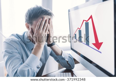 Frustrated stressed shocked business man with financial market chart graphic going down on grey office wall background. Poor economy concept. Face expression, emotion, reaction - stock photo