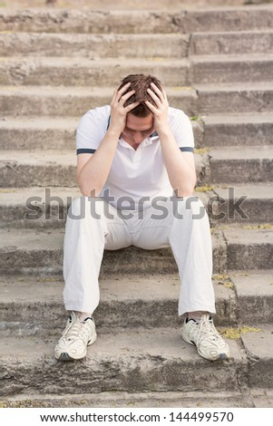 Frustrated stressed young man sitting on stairs outdoor - stock photo