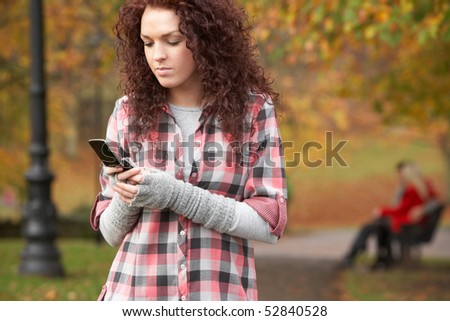 Frustrated Teenage Girl Making Mobile Phone Call In Autumn Landscape - stock photo