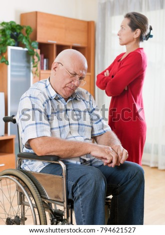 frustrated wife next to   elderly husband in   wheelchair.