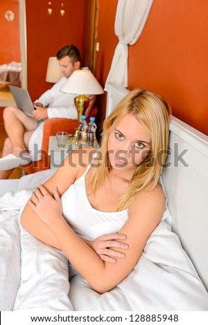 Frustrated woman after argument lying bed husband playing laptop - stock photo