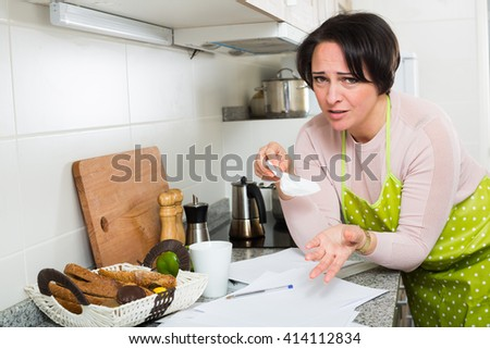 Frustrated woman cannot pay all bills and crying in kitchen - stock photo