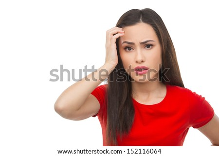 Frustrated woman. Depressed young woman holding her hand in hair and looking at camera while isolated on white