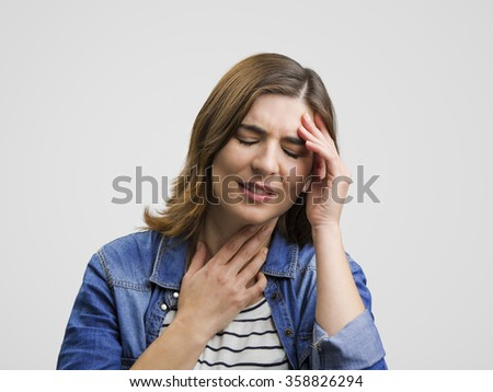Frustrated woman holding head in hands and expressing pain - stock photo