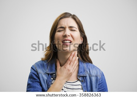 Frustrated woman in pain with a sore throat