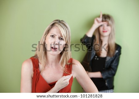 Frustrated woman points at girl showing loser sign - stock photo