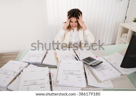 Frustrated Young Accountant Overloaded With Work In Office - stock photo