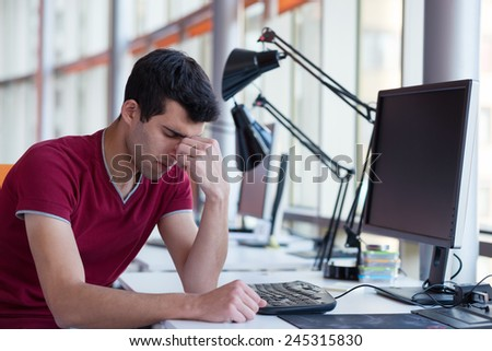 frustrated young business man working on laptop computer at office - stock photo