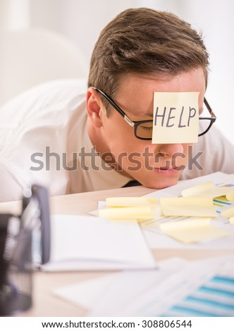 Frustrated young businessman in his office with adhesive note on his forehead. He needs help. - stock photo