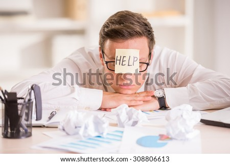 Frustrated young businessman in his office with adhesive note on his forehead. He needs help.