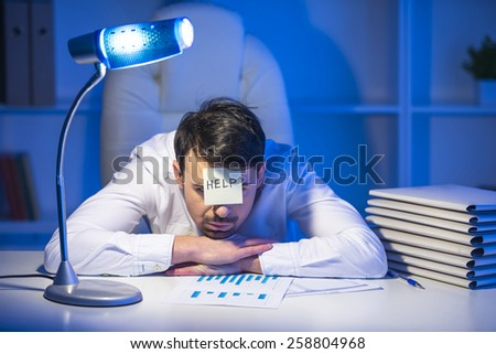 Frustrated young businessman in his office with note on his forehead. He needs help. - stock photo