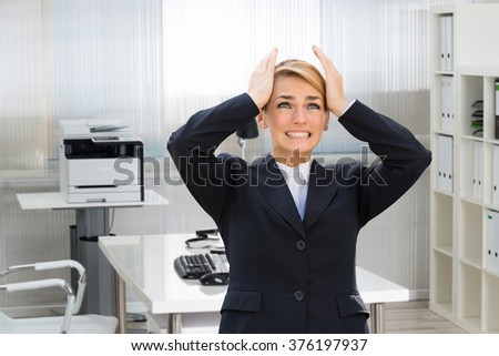 Frustrated young businesswoman suffering from headache in office
