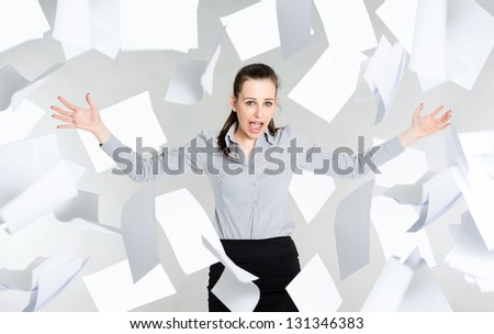Frustrated young businesswoman with falling paper documents, gray background